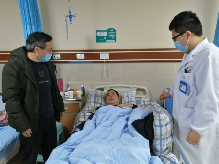 崔建强(左)同值班医生了解患者术后恢复情况